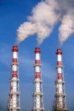 Drie gestreepte industriële pijpen met rook over wolkenloze blauwe hemel Stock Fotografie
