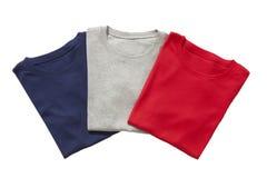 Drie gevouwen geïsoleerde t-shirts Stock Afbeeldingen