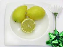 Drie gezonde citroenen op witte plaat en bloem Royalty-vrije Stock Afbeelding