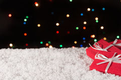 Drie giftdozen op de sneeuw met Kerstmislichten op de achtergrond Royalty-vrije Stock Foto's