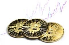 Drie glanzende bitcoinmuntstukken op witte achtergrond met het uitwisselen van grafiek Stock Foto's