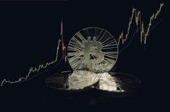 Drie glanzende bitcoinmuntstukken op zwarte achtergrond met het uitwisselen van grafiek Royalty-vrije Stock Fotografie