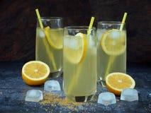 Drie glazen koude eigengemaakte limonade met citroenplakken, ijsblokjes, bruin suiker en stro Stock Afbeelding
