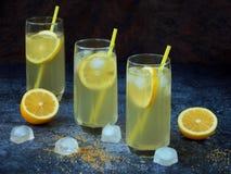 Drie glazen koude eigengemaakte limonade met citroenplakken, ijsblokjes, bruin suiker en stro op donkere achtergrond Stock Afbeelding