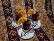 Drie glazen overwogen wijn met kruidige oranje plakken Stock Afbeeldingen