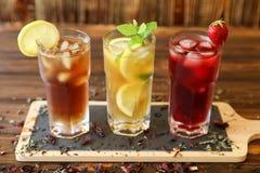Drie glazen verschillende koude thee drinkt zwarte, groen met citroen en munt, hibiscustheeën Stock Afbeelding