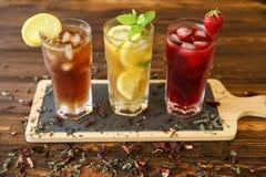 Drie glazen verschillende koude thee drinkt zwarte, groen met citroen en munt, hibiscustheeën Stock Foto's