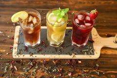 Drie glazen verschillende koude thee drinkt zwarte, groen met citroen en munt, hibiscustheeën Royalty-vrije Stock Fotografie