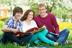 Drie glimlachende jonge studenten in openlucht Stock Fotografie