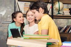 Drie glimlachende kinderen die digitale tablet gebruiken stock afbeeldingen