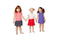 Drie glimlachende meisjes die handen houden Stock Foto's
