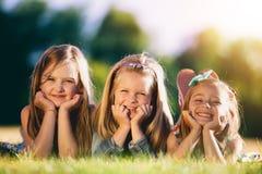 Drie glimlachende meisjes die op het gras in het park leggen Royalty-vrije Stock Afbeelding