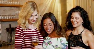 Drie glimlachende vrouwelijke vrienden die selfie terwijl het hebben van dranken 4K 4k nemen stock videobeelden