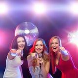 Drie glimlachende vrouwen die en karaoke zingen dansen stock foto