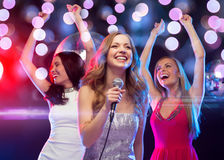 Drie glimlachende vrouwen die en karaoke zingen dansen Stock Afbeeldingen
