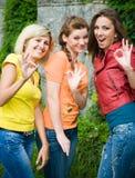 Drie glimlachende vrouwen die okey tonen Royalty-vrije Stock Afbeelding