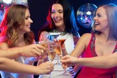 Drie glimlachende vrouwen met cocktails in club royalty-vrije stock afbeeldingen