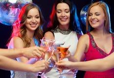 Drie glimlachende vrouwen met cocktails in club Stock Foto's