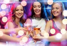 Drie glimlachende vrouwen met cocktails in club Stock Foto