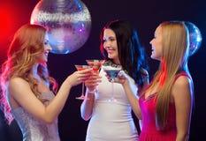 Drie glimlachende vrouwen met cocktails en discobal Stock Foto's