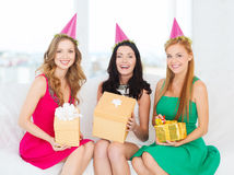 Drie glimlachende vrouwen in roze hoeden met giftdozen Stock Foto