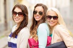 Drie glimlachende vrouwen in zonnebril met zakken royalty-vrije stock foto