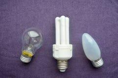 Drie gloeilampen Een witte energy-saving fluorescente bol met vier buizen, een langwerpige gloeiende bol met grijs glas, een rond Stock Foto
