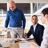 Drie goed geklede, dynamische programmeurs die aan taak samenwerken Stock Afbeelding