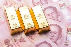 Drie gouden bar met Thaise honderd Bahtrekeningen Stock Afbeelding