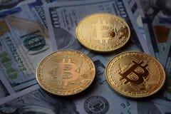 Drie Gouden Bitcoin-Muntstukken op Amerikaanse dollars stock afbeelding