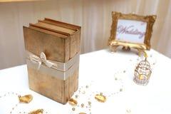 Drie gouden boeken en gouden bruiloftkader Royalty-vrije Stock Afbeelding