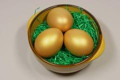Drie gouden eieren in een kom Royalty-vrije Stock Afbeeldingen