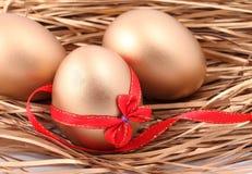 Drie gouden eieren in het nest Royalty-vrije Stock Afbeeldingen