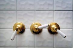 Drie gouden handvatten van de doucheklep stock afbeelding