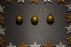 Drie gouden Kerstmisornamenten op zwarte leiachtergrond Stock Afbeeldingen