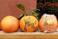 Drie grapefruits op een markt in Tint, Vietnam voor viering van Vietnamees Nieuwjaar De inschrijving is vertaald - Tint royalty-vrije stock foto's