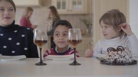 Drie grappige jonge geitjes die bij de lijst met kleine cake en wijnglazen met sap zitten Twee Kaukasische meisjes en Afrikaan stock video