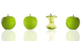 Drie groene appelen en één appelkern Royalty-vrije Stock Afbeeldingen