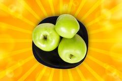 Drie groene appelen op een zwarte plaat Royalty-vrije Stock Afbeelding
