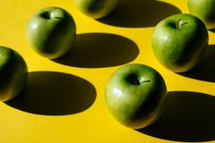 Drie groene appelen op gele achtergrond stock fotografie