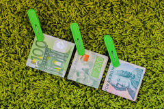 Drie groene bankbiljetten 100 euro 100 Zweedse crownes en 200 Zweedse crownes in groene wasknijpers bij groene achtergrond Royalty-vrije Stock Afbeelding