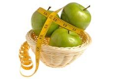 Drie groene die appelen met het meten van band in rieten worden verpakt bas Royalty-vrije Stock Afbeeldingen