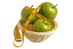 Drie groene die appelen met het meten van band in rieten worden verpakt bas Stock Afbeelding
