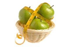 Drie groene die appelen met het meten van band in rieten worden verpakt bas Stock Foto's
