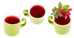 Drie groene mokken met hete geneeskrachtige thee van rozebottels royalty-vrije stock afbeeldingen