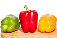 Drie groene paprika's - groen, rood en geel op een scherpe raad Royalty-vrije Stock Foto