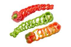 Drie groene paprika's verschillende die kleuren door ringen worden gesneden Stock Afbeeldingen