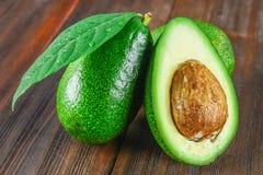 Drie groene ruwe rijpe avocadovruchten en een besnoeiing half met een been met bladeren op een bruine houten lijst Royalty-vrije Stock Fotografie