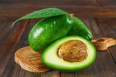 Drie groene ruwe rijpe avocadovruchten en een besnoeiing half met een been met bladeren op een houten scherpe raad op een bruine  Royalty-vrije Stock Foto's