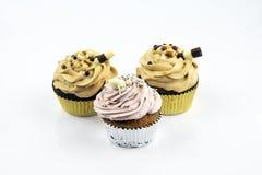 Drie grote en heerlijke die muffins met karamel en aardbeischuim worden gevuld Verfraaid met een zoete buis stock foto's